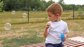 Un niño feliz se está sentando en un banco en el patio y burbujas que soplan en la cámara lenta almacen de metraje de vídeo