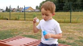 Un niño feliz se está sentando en un banco y burbujas que soplan en la cámara lenta metrajes
