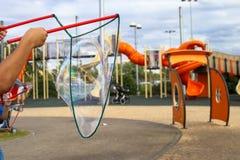 Un niño hace burbujas de jabón grandes en un patio en Tel Aviv con las cuerdas y los palillos Fotos de archivo libres de regalías