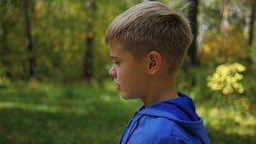 Un niño hermoso está caminando a lo largo del callejón en el parque Actividades al aire libre almacen de metraje de vídeo