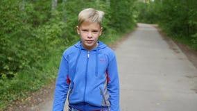 Un niño hermoso está caminando a lo largo del callejón en el parque Actividades al aire libre metrajes