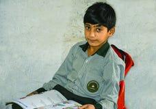 Un niño hermoso que sostiene el libro de escuela Foto de archivo