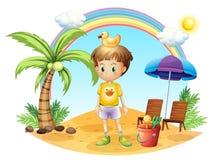 Un niño joven con sus juguetes cerca del árbol de coco Imagenes de archivo