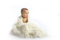 Un niño joven que se sienta en un fondo blanco Foto de archivo libre de regalías