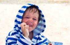 Un niño lindo en una bata de Terry con el dermatitis atópico, demostraciones sus dientes con un finger Un niño con la piel roja s imagen de archivo libre de regalías