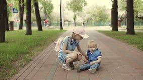 Un niño lindo se está sentando en la trayectoria en el parque metrajes