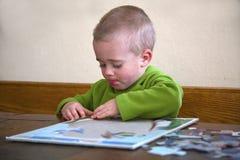 Niño que trabaja en un rompecabezas Imagen de archivo libre de regalías