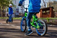 Un niño monta una bici del verde del ` s de los niños imagenes de archivo
