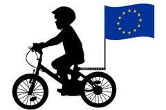 Un niño monta una bicicleta con la bandera de unión europea Foto de archivo