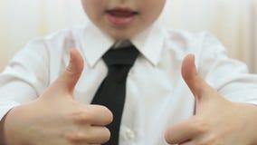 Un niño muestra una figura bajo la forma de pulgar para arriba almacen de video