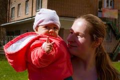 Un niño muy serio en miradas rosadas en la cámara y las demostraciones un finger Se sienta con la mamá en sus brazos talking imagen de archivo