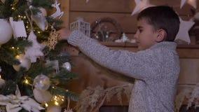 Un niño pequeño adorna un árbol de navidad con una bola hermosa HD metrajes