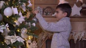 Un niño pequeño adorna un árbol de navidad con una bola hermosa que tiene un buen humor metrajes