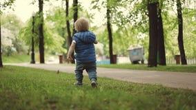 Un niño pequeño alegre está corriendo alrededor en el parque almacen de video