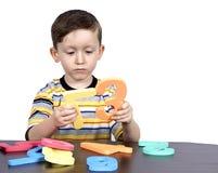 Un niño pequeño aprende los números fotografía de archivo libre de regalías