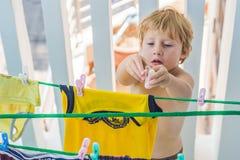Un niño pequeño ayuda a su madre a colgar para arriba viste Imágenes de archivo libres de regalías