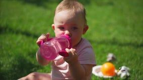 Un niño pequeño bebe el agua de una botella del plástico del ` s de los niños metrajes