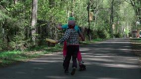 Un niño pequeño coge a la muchacha que monta en pcteres de ruedas Lento-MES metrajes