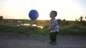 Un niño pequeño como un jugador de voleibol bate de una bola en la cámara lenta al aire libre almacen de video