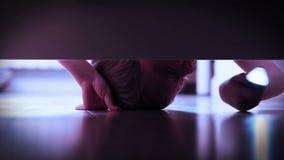 Un niño pequeño con la antorcha del bolsillo, buscando algo alrededor debajo de la cama almacen de video