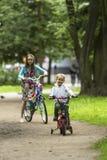 Un niño pequeño con su paseo de la hermana bikes en el parque Diversión Fotografía de archivo libre de regalías