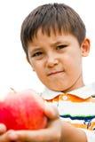Un niño pequeño con una manzana Imagen de archivo libre de regalías