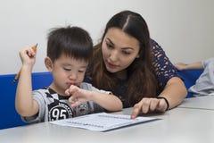 Un niño pequeño de enseñanza de la maestra, explicando cómo escribir en sala de clase en la escuela fotografía de archivo libre de regalías