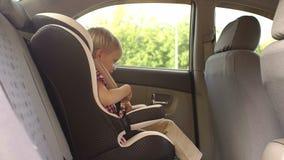 Un niño pequeño desabrocha sus cinturones de seguridad en un asiento de carro del niño en el coche almacen de video