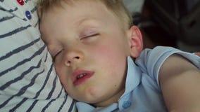 Un niño pequeño duerme en los brazos de su madre en un coche o un autobús durante un viaje, primer almacen de metraje de vídeo