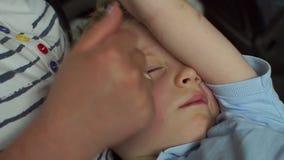Un niño pequeño duerme en los brazos de su madre en un coche o un autobús durante un viaje, primer metrajes