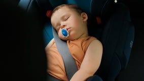 Un niño pequeño duerme en una silla Sistemas de la seguridad de los niños en coches metrajes