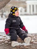Un niño pequeño en botas se sienta en un árbol caido grande en invierno foto de archivo