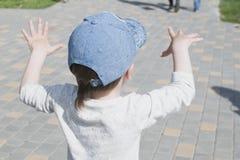 Un niño pequeño en la ciudad juega cerca de la fuente con agua Imagenes de archivo