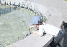 Un niño pequeño en la ciudad juega cerca de la fuente con agua Foto de archivo