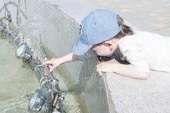 Un niño pequeño en la ciudad juega cerca de la fuente con agua Fotos de archivo