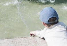 Un niño pequeño en la ciudad juega cerca de la fuente con agua Fotografía de archivo