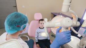 Un niño pequeño en la odontología que se sienta en la silla paciente, el dentista gira la lámpara y la apertura de su boca almacen de video
