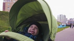 Un niño pequeño en ropa caliente está montando en un cochecito de niño almacen de metraje de vídeo
