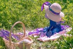 Un niño pequeño en un sombrero se sienta en un campo sorpresa El concepto de verano imagenes de archivo