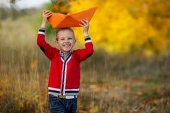 Un niño pequeño en un suéter rojo está aplazando un barco del papel grande Fotos de archivo libres de regalías
