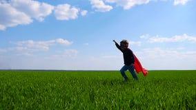 Un niño pequeño en un traje del super héroe da vuelta alrededor a funcionamiento a través de un campo verde que lleva a cabo su m almacen de metraje de vídeo