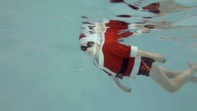 Un niño pequeño en un traje y un sombrero Santa Claus nada bajo el agua en la piscina con los vidrios para nadar y mirar la cámar almacen de video