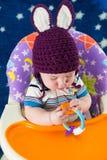 Un niño pequeño en un sombrero hecho punto con los oídos de conejo juega Foto de archivo libre de regalías