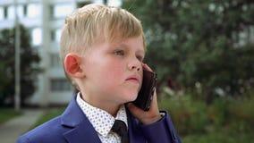 Un niño pequeño en una chaqueta azul con el lazo habla en el teléfono negro en la calle