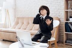 Un niño pequeño en vidrios y traje se presenta como hombre de negocios El muchacho oscuro-cabelludo juega a un hombre rico imagen de archivo libre de regalías