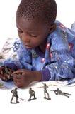 Un niño pequeño enfermo que juega con los hombres del ejército Imagenes de archivo