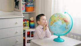 Un niño pequeño está buscando un lugar en el globo en donde él creció metrajes