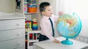 Un niño pequeño está buscando un lugar en el globo en donde él creció almacen de video