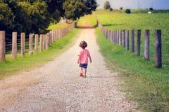 Un niño pequeño está caminando solamente en la granja de la carretera nacional en un Br foto de archivo libre de regalías