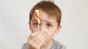 Un niño pequeño está comiendo un caramelo brillante en un palillo, una piruleta metrajes